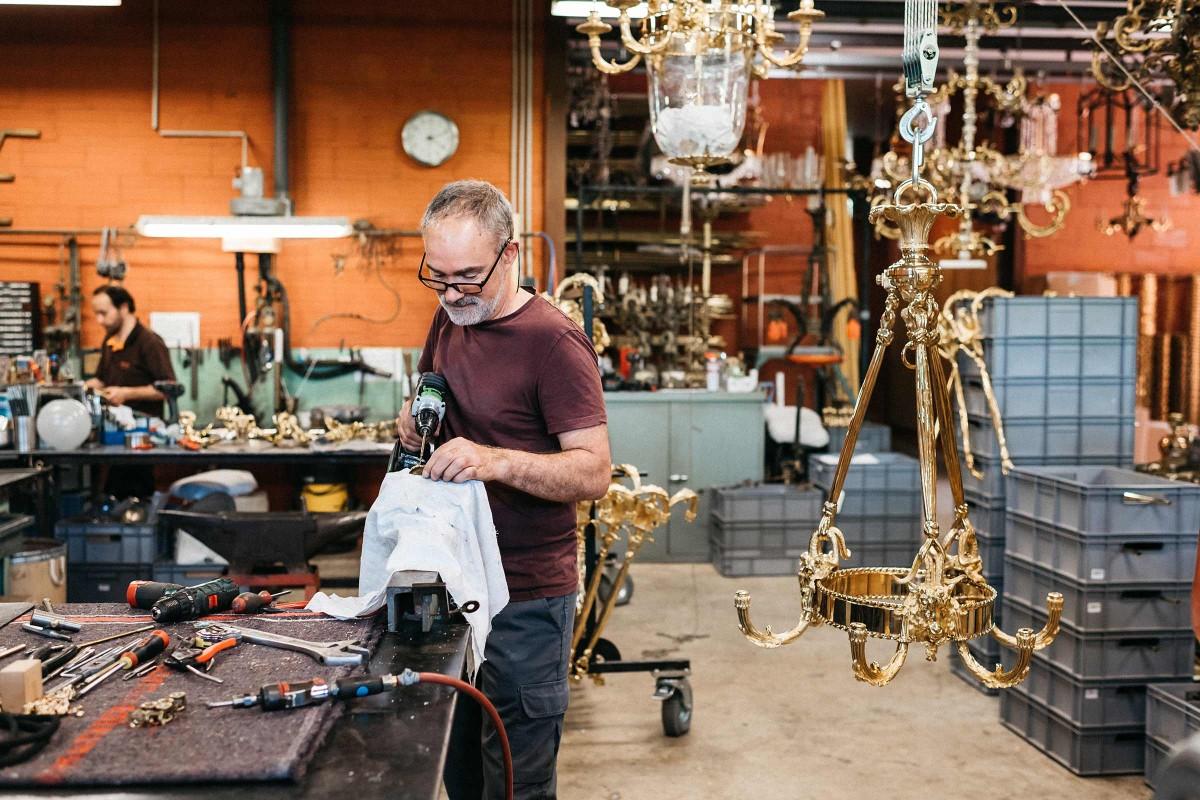 Mit einer Bohrmaschine versieht Joaquim Mendes einen Teil des Kronleuchters mit Löchern.