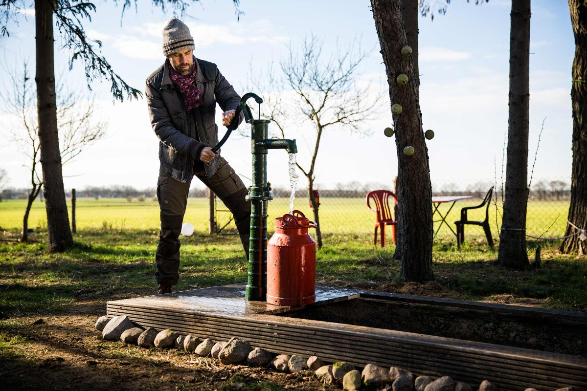 Autor Sascha Borrée pumpt zum ersten Mal Wasser aus seinem selbst gebauten Gartenbrunnen.