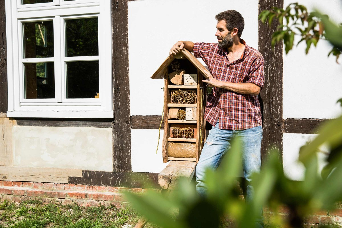 Autor Sascha Borrée steht neben seinem selbst gebauten Insektenhotel und wartet auf erste Bewohner.