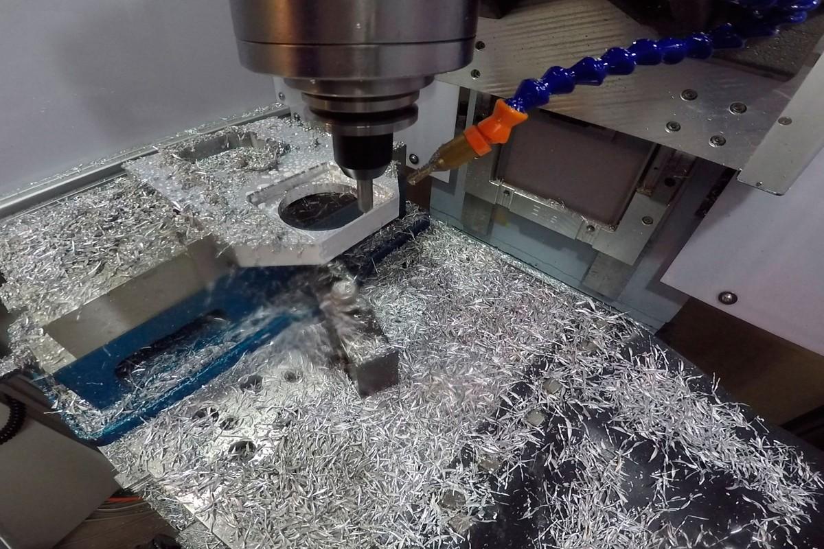 Eine CNC Fräse bearbeitet ein Stahlteil, Späne fliegen umher