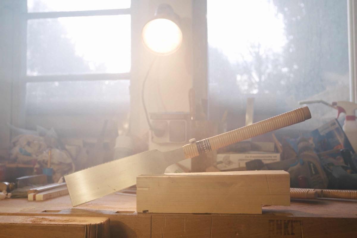 Eine Ryoba Japansäge steckt in einem Holzblock in der Werkstatt.