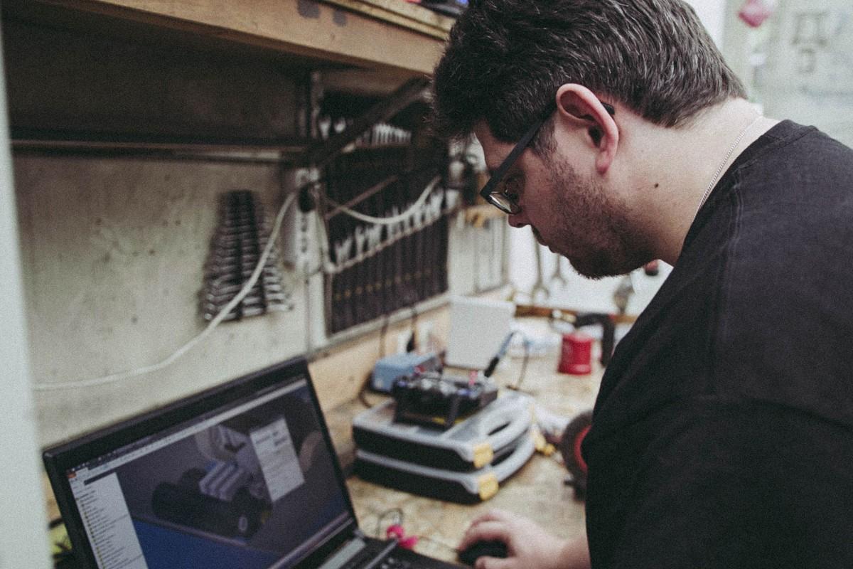 Niels Schotten programmiert einen Roboter an seinem Laptop in der Werkstatt;