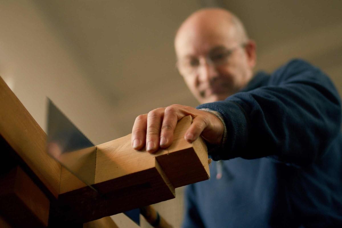 Heiner zersägt ein Stück Holz mit einer Japansäge.
