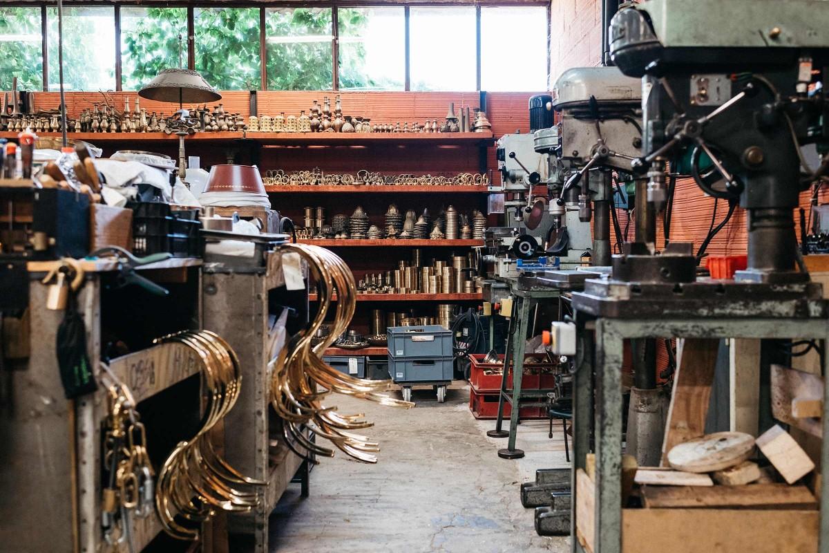 Das Atelier von Kronleuchterhersteller Régis Mathieu: ockerrote Wände, Werkbänke, Leuchterteile und Werkzeuge.