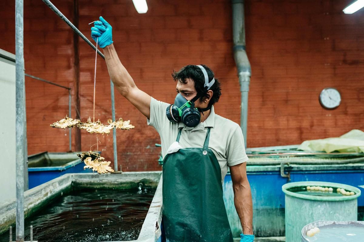 In einem separaten Raum in Régis Mathieus Kronleuchteratelier in Südfrankreich sind längliche Tröge mit 70° C heißen Flüssigkeiten gefüllt, um die Kronleuchter zu vergolden. An der Oberfläche schwimmen Tischtennisbälle, die ein zu schnelles Verdampfen der Flüssigkeit verhindern.